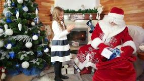 Santa daje boże narodzenie prezentowi dla małej dziewczynki, dzieciak odwiedza świętego Nicolas zimy siedzibę, teraźniejszość zdjęcie wideo