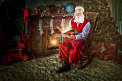 Santa dans la chaise de basculage avec le livre Photos libres de droits