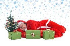 Santa de sono no vermelho sob a árvore Fotografia de Stock