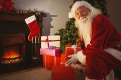 Santa de sourire livrant des cadeaux au réveillon de Noël Photo stock