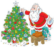 Santa decorates a Christmas tree. Father Christmas decorating a fir to holiday, isolated on a white background Royalty Free Stock Photos