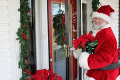 Santa Delivers a Poinsettia Plant Royalty Free Stock Photos
