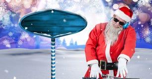 Santa DJ e letreiro de madeira no inverno do Natal ajardina Imagens de Stock