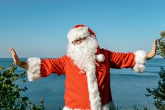 Santa doing exercises on the ocean. Traditional red outfit and relaxing on the beach stock photos