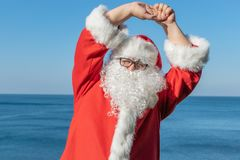 Santa doing exercises on the ocean. Traditional red outfit and relaxing on the beach. Santa doing exercises on the ocean stock photos
