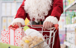 Santa doing grocery shopping. Santa Claus doing grocery shopping at the supermarket, he is pushing a full cart, hands detail, Christmas and shopping concept Stock Photography