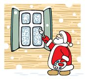 Santa draws patterns on the window. Royalty Free Stock Image