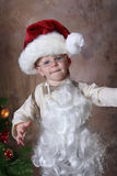 Santa Dress Up. Toddler Dressed up as Santa, in hat, beard and glasses royalty free stock image