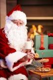 Santa drinking milk eating chocolate chip cookies. Happy Santa Claus sitting at fireplace drinking milk eating chocolate chip cookies, looking at camera, winking Royalty Free Stock Photos