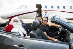 Santa And Driver In Convertible With Jet in stock images