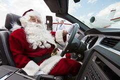 Santa Driving Convertible At Airport Terminal. Portrait of Santa driving convertible with pilot and airhostess standing in background at airport terminal Royalty Free Stock Image
