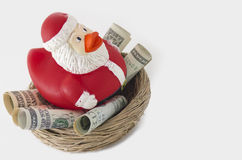 Santa duck Savings for Christmas. Santa rubber ducky sitting in a nest of money savings for Christmas. Concept is about spending money and saving for the holiday Stock Image