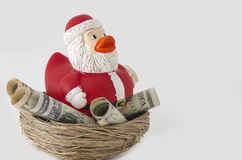 Santa duck Savings for Christmas. Santa rubber ducky sitting in a nest of money savings for Christmas. Concept is about spending money and saving for the holiday Stock Photo
