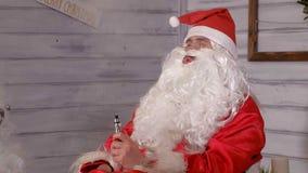 Santa dymi wytarcia obsiadanie w krześle Obrazy Stock