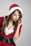 Santa dziewczyna patrzeje w dół i szuka dla coś gubjącego w czerwonym Bożenarodzeniowym hoodie kostiumu Obraz Stock