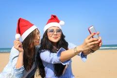Santa dziewczyny biorą selfie na pogodnej plaży zdjęcia royalty free