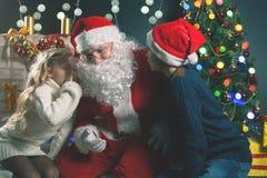 Santa e bambini intorno all'albero di Natale decorato Lista di desideri Fotografie Stock
