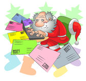 Santa and e-mail. Santa Claus sits at a laptop and receives letters of different color by e-mail Stock Photos
