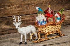 Santa e pupazzo di neve in una slitta della renna con i regali Immagine Stock