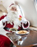 Santa Eating Cookies While Holding-Melkglas binnen Stock Afbeeldingen