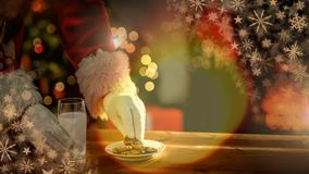 Santa eating cookies and milk at Christmas home and glowing warmth