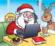 Santa At eine Kaffeestube auf einem Laptop Lizenzfreie Stockfotos
