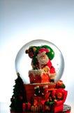 Santa en un snowglobe que entra la chimenea Foto de archivo libre de regalías