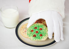Santa entregam o alcance para o bolinho do Natal fotografia de stock royalty free