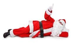 Santa está apontando seu dedo em um objeto Imagem de Stock