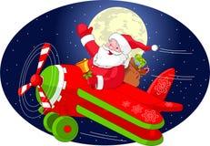 Santa está volando en un aeroplano Imágenes de archivo libres de regalías