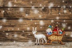 Santa et bonhomme de neige dans un traîneau de renne avec des cadeaux Images stock