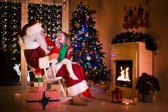 Santa et petite fille sous l'arbre de Noël Photos stock