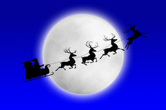Santa et ses rennes conduisant contre la lune Photos stock
