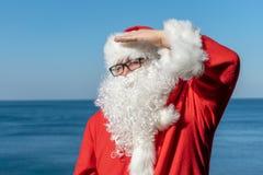 Santa examine la distance, se tenant sur l'océan Équipement rouge traditionnel et détente sur la plage photo libre de droits