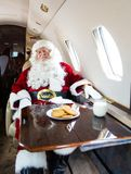 Santa With Eyes Closed Relaxing In Private Jet. Man in santa costume relaxing on private jet Royalty Free Stock Photo