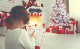 Santa för bokstav för barnflickahandstil hem- near julgran Arkivbild