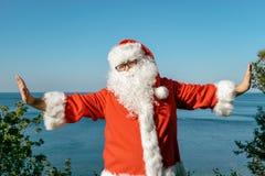 Santa faisant des exercices sur l'océan Équipement rouge traditionnel et détente sur la plage photos stock