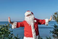 Santa faisant des exercices sur l'océan Équipement rouge traditionnel et détente sur la plage photographie stock