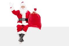 Santa faisant des gestes le bonheur posé sur un panneau Images libres de droits