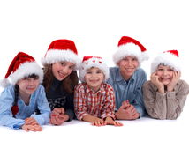Santa family. A group of smiling children with Santa Claus hats, white background Stock Images