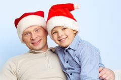 Santa father and son. Father and son in Santa hats smiling and looking at camera Stock Images