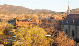 Santa Fe New Mexico at Sunset. The Loretto Chapel is on the right of the photograph. There are trees in the foreground and buildings with the characteristic royalty free stock photography