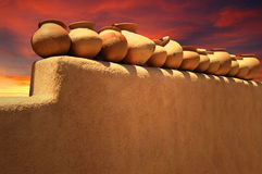 Santa Fe Pottery. A row of decorative pots sit line an adobe wall against a colorful sky in Santa Fe, New Mexico Stock Photo