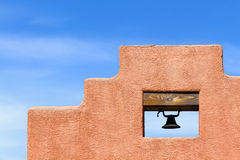 Adobe Mission. Santa Fe style adobe wall and bell against blue sky in New Mexico Royalty Free Stock Photography