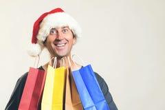 Santa felice con i sacchetti della spesa, isolati su bianco Copi lo spazio Concetto di acquisto, di vendite e di sconti di Natale fotografia stock
