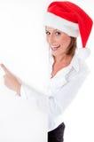 Santa femenino que señala abajo en la cartelera en blanco Fotografía de archivo