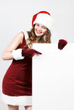Santa femenino que sostiene una tarjeta del blanco de la Navidad Imágenes de archivo libres de regalías