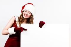 Santa femenino que sostiene una tarjeta del blanco de la Navidad Fotografía de archivo
