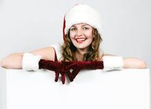 Santa femenino que sostiene una tarjeta del blanco de la Navidad Imagen de archivo libre de regalías