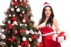 Santa femminile che fa una pausa un albero di Natale Immagini Stock